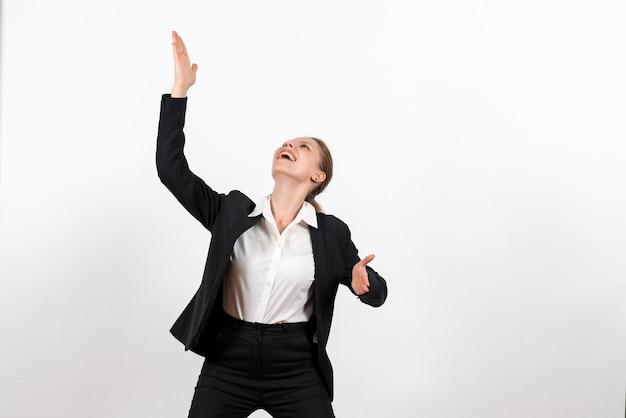 Вид спереди молодая женщина в строгом классическом костюме приветствует кого-то с улыбкой на белом фоне деловая женщина работает женский рабочий костюм