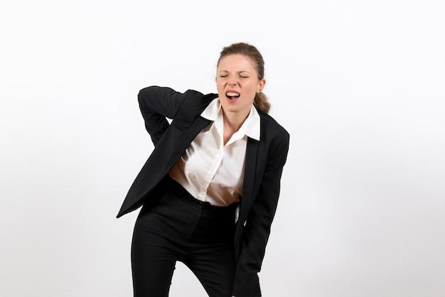 Вид спереди молодая женщина в строгом классическом костюме, имеющая проблемы со спиной на белом фоне, рабочая женщина, деловой костюм, рабочая женщина