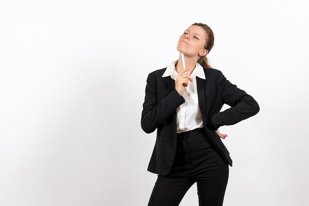 Вид спереди молодая женщина в строгом классическом костюме, держащая ручку и думая на белом фоне, женщина, работа, костюм, бизнес, женская работа