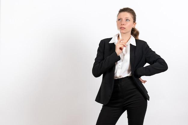 Вид спереди молодая женщина в строгом классическом костюме, держащая ручку на белом фоне, женщина, работа, бизнес, женский рабочий костюм