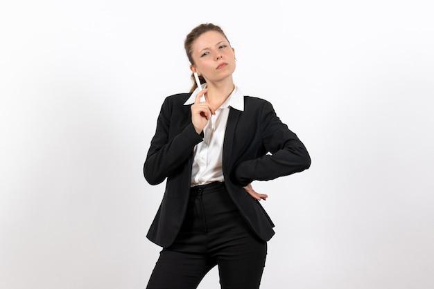 Вид спереди молодая женщина в строгом классическом костюме, держащая ручку на белом фоне, женский рабочий костюм, деловая женская работа