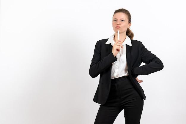 Вид спереди молодая женщина в строгом классическом костюме, держащая ручку на белом столе, женский рабочий костюм, деловая женская работа