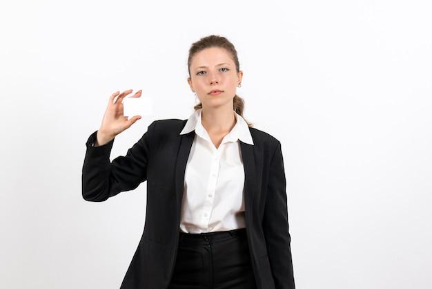 Вид спереди молодая женщина в строгом классическом костюме, держащая белую карточку на белом фоне, работа, бизнес, женский рабочий костюм, женщина