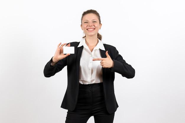 Вид спереди молодая женщина в строгом классическом костюме, держащая белую карточку на белом фоне, работа, бизнес, работа, костюм, женщина