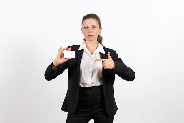 Вид спереди молодая женщина в строгом классическом костюме, держащая белую карточку на белом столе, деловая женщина, рабочий костюм, женщина