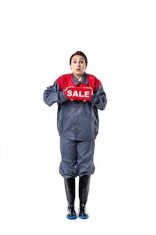 白い背景の上の赤いセールのネームプレートを保持している制服を着た若い女性の正面図