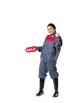 販売ネームプレートを保持し、白い背景に笑みを浮かべて制服を着た若い女性の正面図