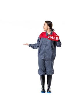 白い背景の上の販売ネームプレートを保持している制服を着た若い女性の正面図