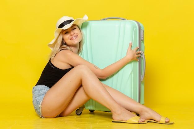 黄色の壁の色の女の子の女性の旅旅行の海で幸せを感じて彼女の緑のバッグを抱いて座っている休暇中の若い女性