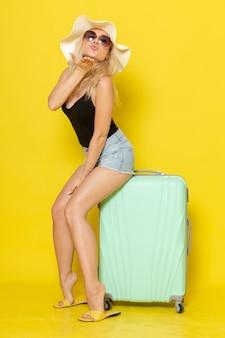 黄色の壁の色の女の子の女性の旅の旅の海に空気のキスを送信するバッグに座って休暇中の若い女性の正面図
