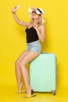 Вид спереди молодая женщина в отпуске, сидя на сумке, используя телефон на желтой стене, цветная девушка, женщина, путешествие, путешествие на море