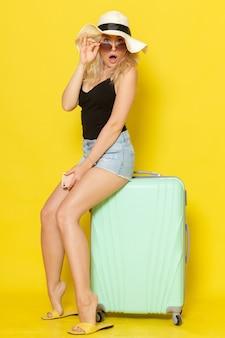 노란색 벽 색상 소녀 여성 여행 여행 바다에 녹색 가방에 앉아 휴가에 전면보기 젊은 여성