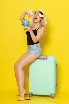 黄色の壁の色の女性の旅旅行海の太陽に地球儀を保持している彼女の緑のバッグに座って休暇中の若い女性の正面図