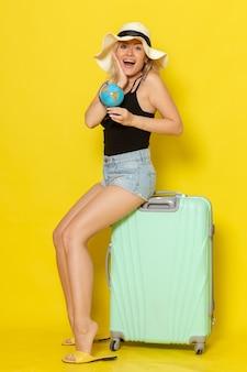 黄色の壁に地球儀を保持している彼女の緑のバッグに座って休暇中の若い女性の正面図女性の旅旅行海色太陽