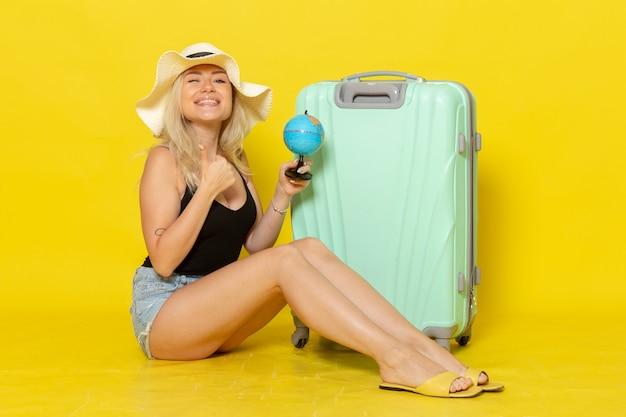 Вид спереди молодая женщина в отпуске сидит со своей зеленой сумкой, держа глобус на желтой стене, женское путешествие, путешествие, цвет моря, солнце
