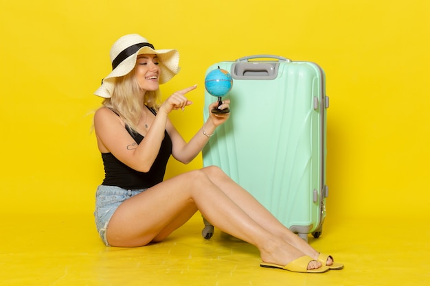 黄色の壁に地球儀を保持している彼女の緑のバッグと一緒に座っている休暇中の若い女性の正面図