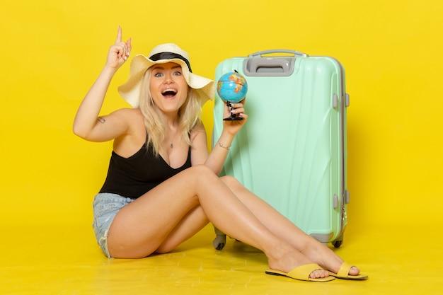 Вид спереди молодая женщина в отпуске, сидящая со своей зеленой сумкой, держащая глобус на желтой стене, женская поездка, отпуск, путешествие, цвет моря, путешествие, солнце