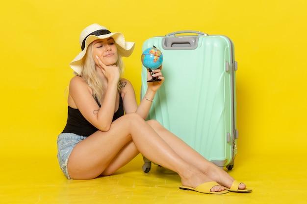 黄色の壁の女性の旅旅行海の色の太陽を考えて地球儀を保持している彼女の緑のバッグと一緒に座って休暇中の若い女性の正面図