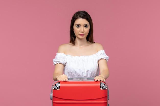 淡いピンクの背景に彼女のバッグを持って休暇中の若い女性の正面図海外海の旅旅行旅行の航海