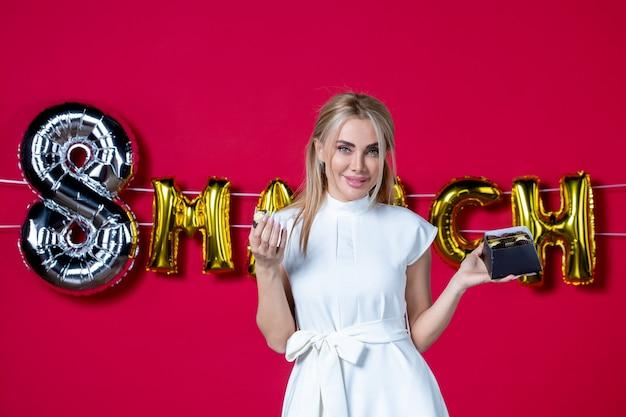 빨간색 비즈니스 재미 휴가에 초콜릿 사탕과 흰색 드레스에 전면 보기 젊은 여성