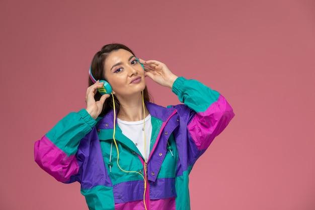 ピンクの壁で音楽を聴いている白いシャツ色のコートの正面図若い女性、写真色の女性のポーズモデル