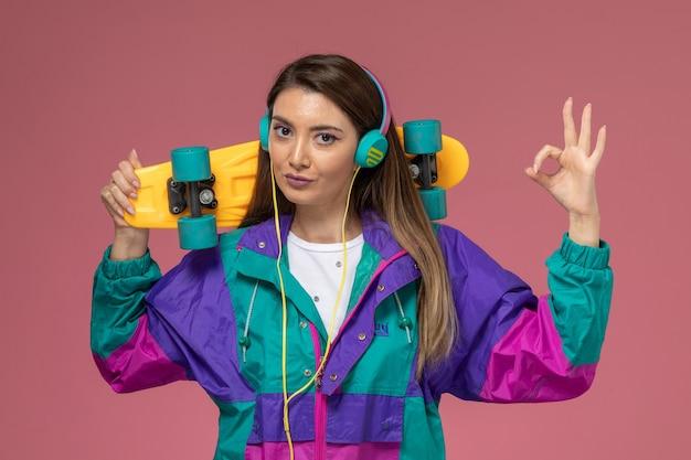 スケートボードを保持している白いシャツのカラフルなコートの正面図若い女性