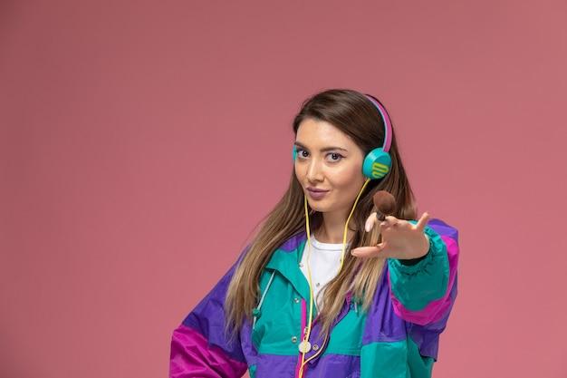 ピンクの壁で音楽を聴く白いシャツのカラフルなコートの正面図若い女性