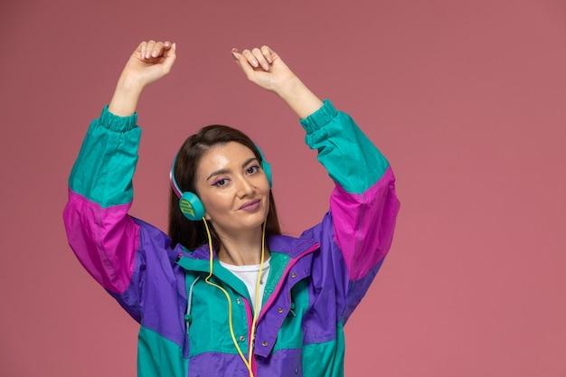 ピンクの壁の写真の色の女性のポーズモデルで踊る音楽を聴く白いシャツのカラフルなコートの正面図若い女性