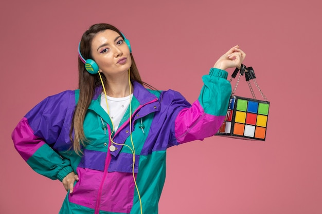 분홍색 벽 사진 색상 여자 포즈 모델에 음악을 듣고 흰 셔츠 화려한 코트에 전면보기 젊은 여성