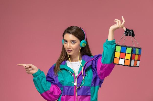 ピンクの壁の写真の色の女性のポーズモデルで音楽を聴いている白いシャツのカラフルなコートの正面図若い女性