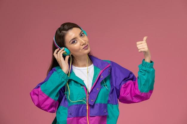淡いピンクの机の上で笑顔で音楽を聴いて白いシャツのカラフルなコートを着た若い女性の正面図