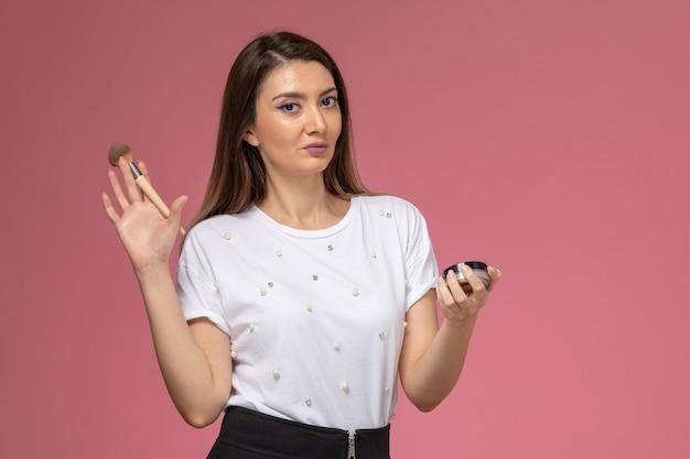 淡いピンクの机の上の彼女のメイクアップをしている白いシャツの正面図若い女性女性美容モデル女性ポーズ