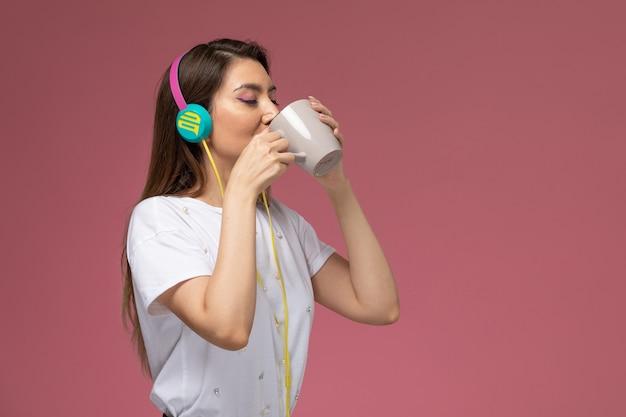 Вид спереди молодая женщина в белой рубашке пьет кофе, слушая музыку на розовой стене модельная женщина