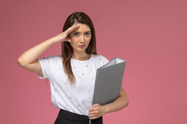 淡いピンクの壁に灰色のファイル、モデルの女性を保持している白いシャツの正面図若い女性