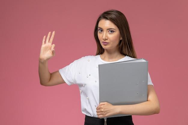 ピンクの壁に灰色のファイルを保持している白いシャツの正面図若い女性、カラー女性ポーズモデル女性