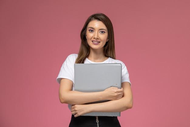 분홍색 벽에 미소로 회색 파일을 들고 흰 셔츠에 전면보기 젊은 여성, 컬러 여자 포즈 모델 여자