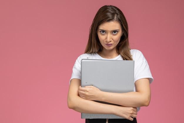 淡いピンクの壁に灰色のファイルを保持している白いシャツの正面図若い女性、モデルの女性のポーズ