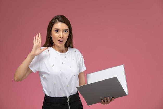 Вид спереди молодая женщина в белой рубашке держит серые файлы, читает их на светло-розовой стене, женщина модель позирует