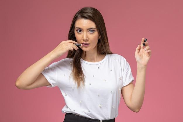 ピンクの壁にメイクアップ鉛筆を保持している白いシャツの正面図若い女性、カラー女性モデルポーズの女性
