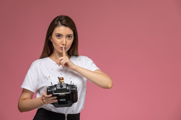 Вид спереди молодая женщина в белой рубашке, держащая пульт дистанционного управления на розовой стене, цветная женщина-модель