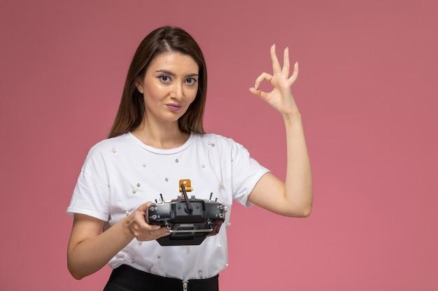 Вид спереди молодая женщина в белой рубашке, держащая пульт дистанционного управления на розовой стене, цветная модель женщины