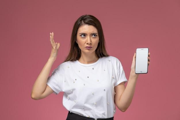 淡いピンクの壁にスマートフォンを保持している白いシャツ、女性モデルの女性のポーズ