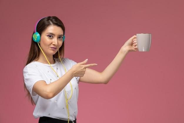 ピンクの壁で音楽を聴いている白いシャツの正面図若い女性、カラーモデルの女性ポーズの女性
