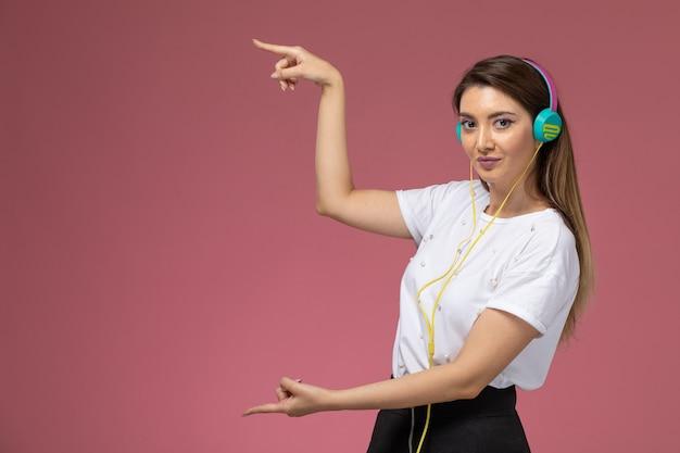 Вид спереди молодая женщина в белой рубашке, слушающая музыку на розовой стене, цветная женщина-модель