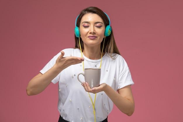 Вид спереди молодая женщина в белой рубашке, слушающая музыку, пахнущую кофе на розовой стене, цветная женщина-модель