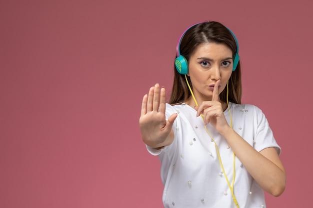 ピンクの壁に彼女の色のイヤホンを介して音楽を聴いている白いシャツの正面図若い女性、色の女性モデルのポーズの女性