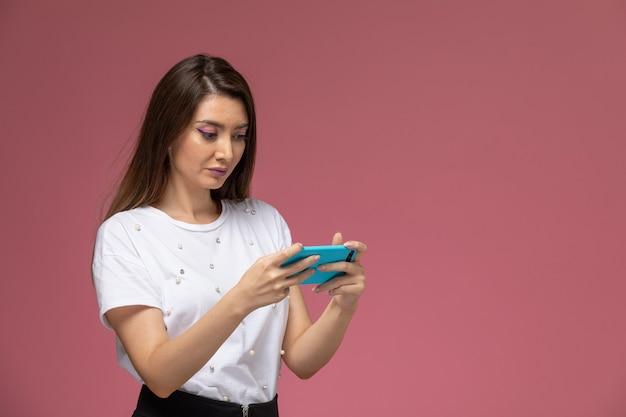 淡いピンクの壁、モデルの女性のポーズで彼女の携帯電話でゲームをしている白いシャツの正面図若い女性