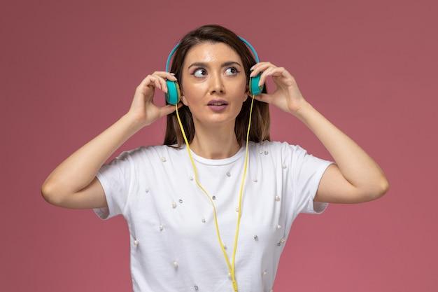 ピンクの壁、色の女性モデルでポーズをとって音楽を聴いて白いシャツを着た若い女性の正面図