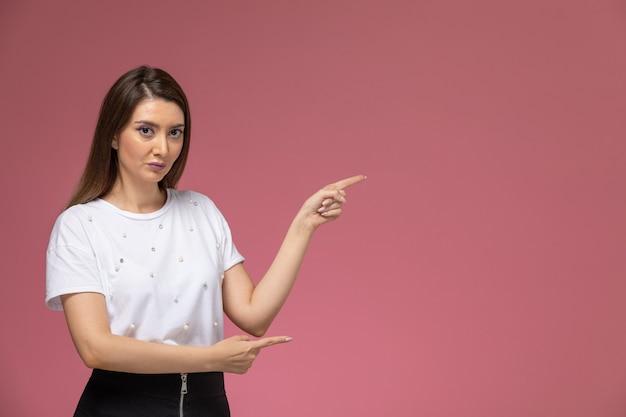 ピンクの壁に上げられた手でポーズをとる白いシャツの正面図若い女性、カラー女性モデルポーズの女性