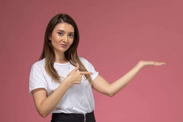 ピンクの壁、色の女性モデルに上げられた手でポーズをとって白いシャツの正面図